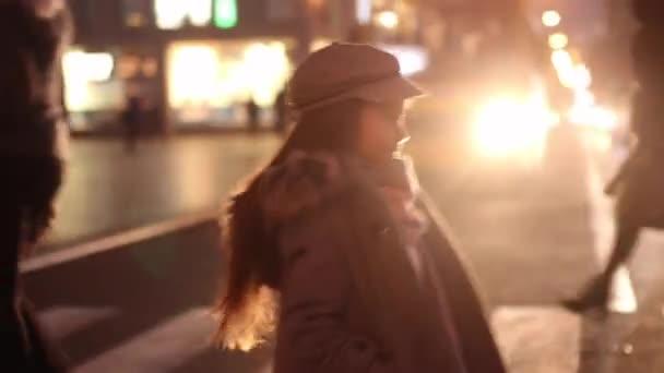 Dítě dívka v kabát, čepici a šálu je chůze po silnici na přechod pro chodce na pozadí reflektorů aut a městské ulici večer.