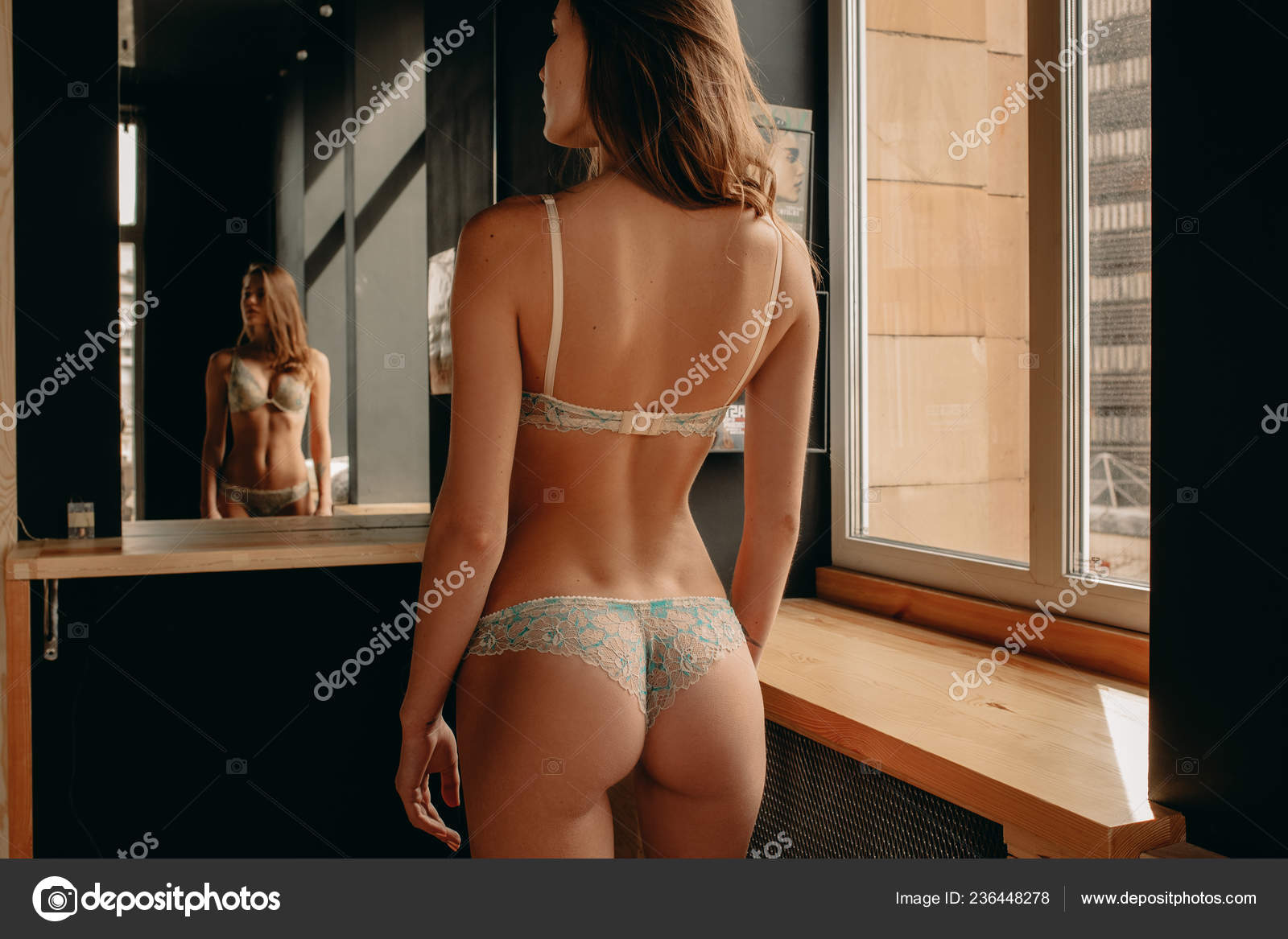 Naked woman in bathroom standing in front of mirror