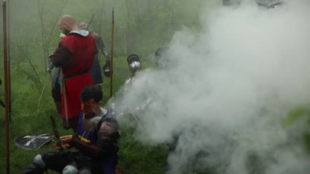 Battle squad of medieval knights of the Crusaders rest on the halt against background of smoke in the forest.