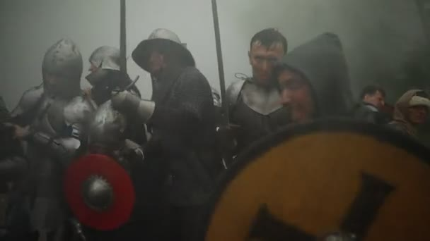 Combat squad of medieval knights of the Crusaders fights with the enemy with swords in misty morning.