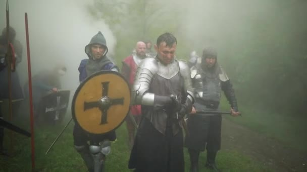 Combat squad of medieval knights of the Crusaders stand in armors and helmets with their swords and shields preparing to attack  against background of smoke in the forest.