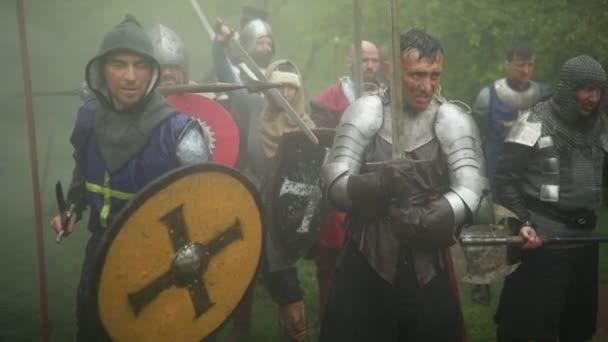 Kampfflugzeuge mittelalterlicher Kreuzritter stehen in Rüstungen mit Schwertern und Schilden und rennen vor nebligem Waldhintergrund zum Angriff.