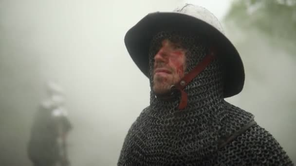 Portrait of medieval knight in armor with blood and wounds on his face on the background of the misty forest  in the rain.