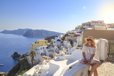 Blonde woman looking at cityscape of Oia village in Santorini island, Greece