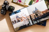 Fotografie Album with photos of travel and vintage old camera on a background of old maps