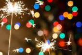 Bengal fire sparkler and colorful bokeh, new year background