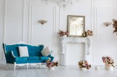 Photo Classic blue sofa in luxurious white room. artificial fireplace