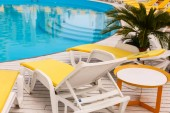 swimming pool with yellows sun lounger