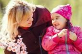 Fotografie Kleines Mädchen anwesend, um ihre Mutter zu Hause zu geben. Muttertag-Konzept Mutter gibt ein kleines Mädchen Blumen