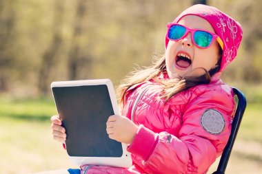 Little girl with tablet pc and headphones listening to music or watching video in summer park