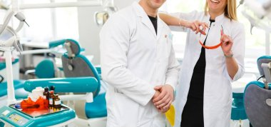 Portrait of a confident male and female dentists smiling at dental clinic looking at camera