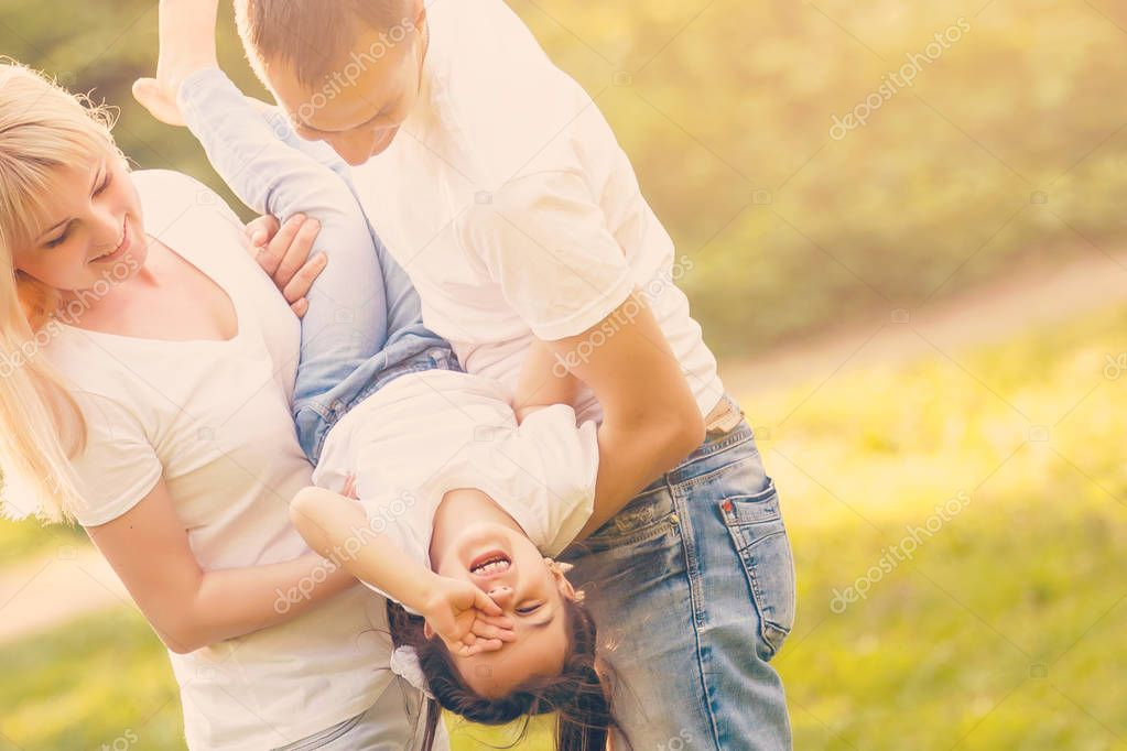 The mother and father hold their daughters upside down