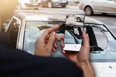 Close up hand of woman holding smartphone and take of car accident