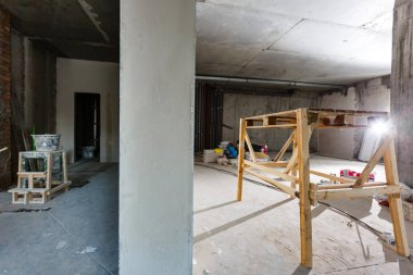 Newly renovated generic empty office space with leftover materials and ladder in foreground