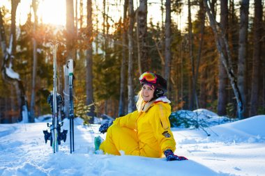 Thoughtful girl with mountain skiing sitting on a ski slope and looks into the distance