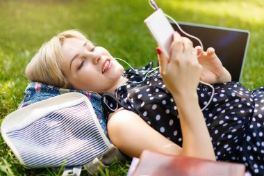 Woman lay down or relaxing on green grass listening to music