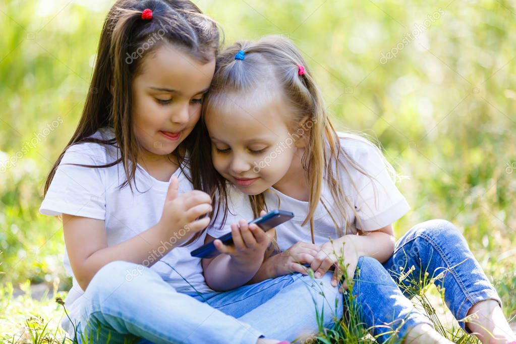 Portrait of two cute girls posing at park with mobiles