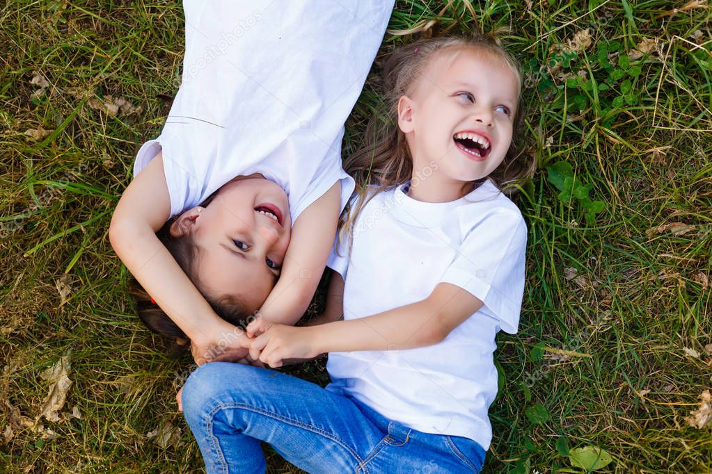 Two little girls in white T-shirts lay on the grass in the park. view from above