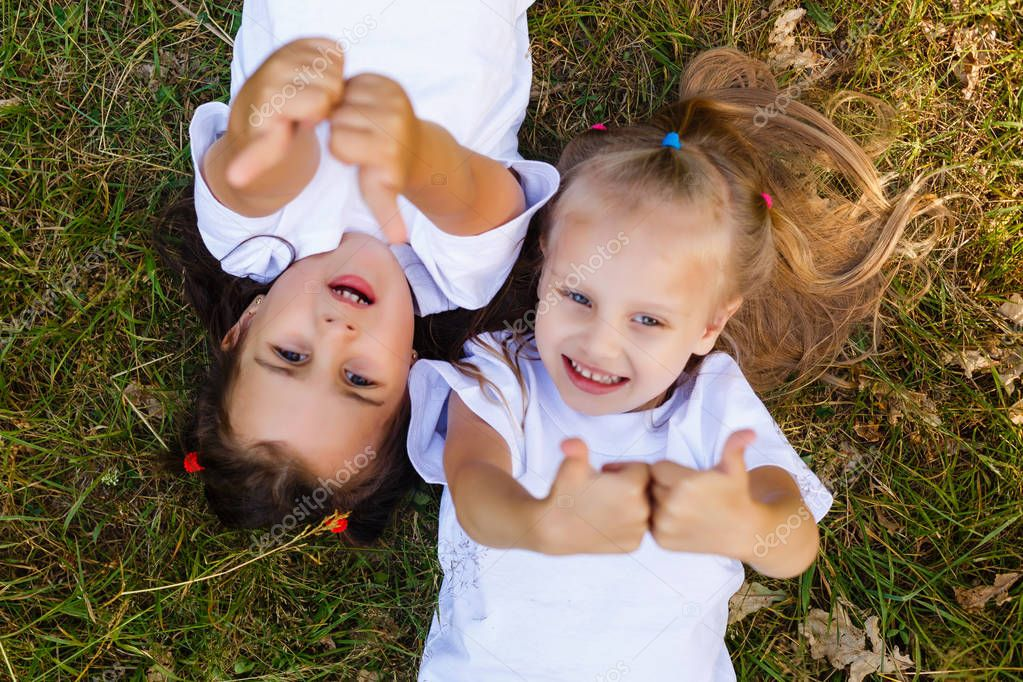 Two little girls in white T-shirts lay on the grass in the park and show the likes. view from above