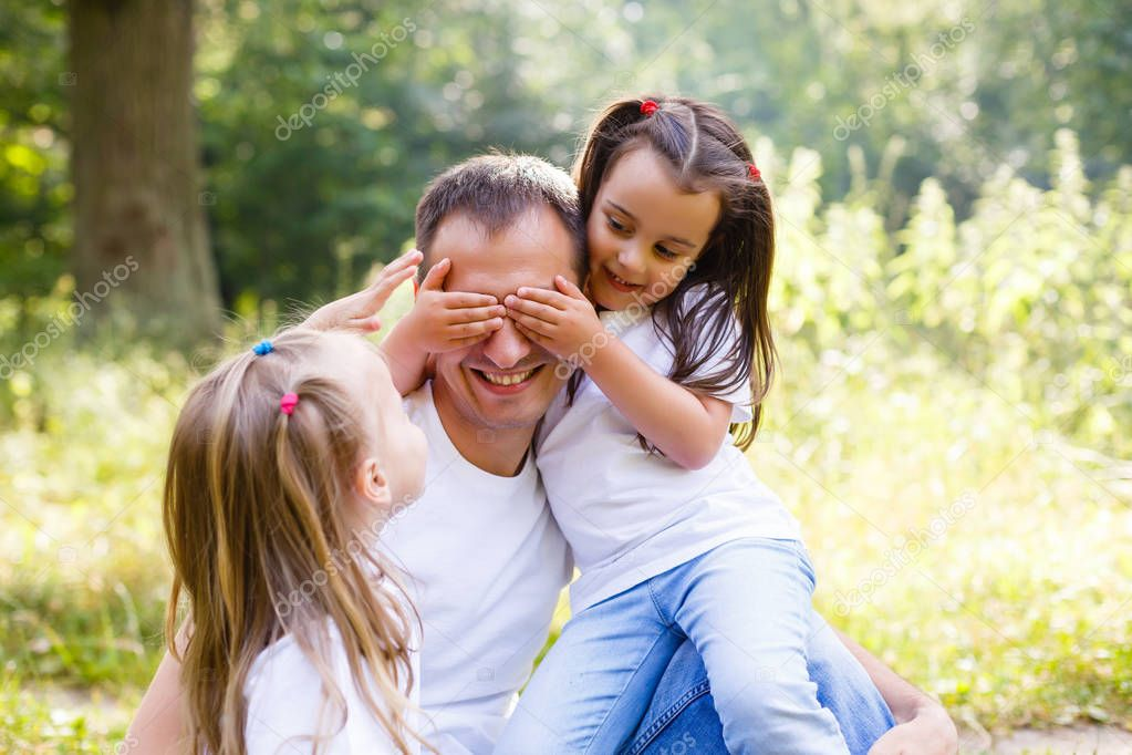 Happy dad and two little daughters having fun sitting on green garden, covering eyes
