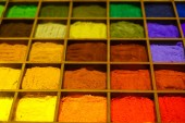 Colorful powder in wooden boxes on display case