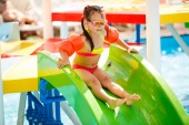 aqua park, Girl with glasses slide down on water slide