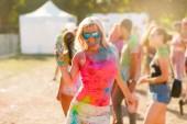 Šťastná dívka, která nosí sluneční brýle na Holi festival barev portrét
