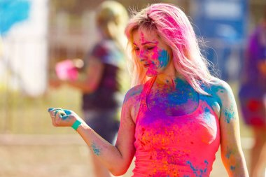 happy young woman holding colorful paint in hands and smiling with closed eyes while standing in field at holi festival