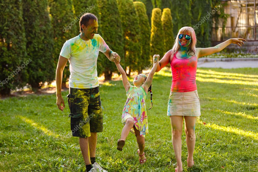 Happy young family with daughter playing in green park and showering with paints