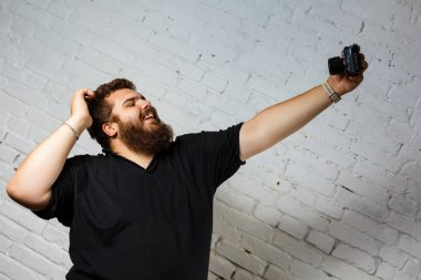 Fat man in black photograph himself with a camera on a white background
