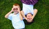 divertimento estivo. vista dallalto di due bambini carini fare facce e sorridente mentre sdraiato sullerba verde insieme