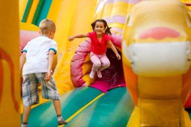 Joyful little girl playing on a trampoline.