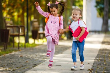 Two beautiful little girls going to school holding hands. Back to school