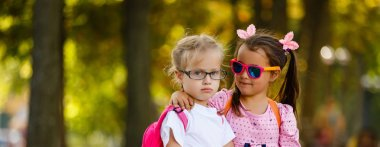 two little girls in glasses go to school