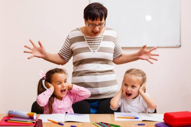 Stressed teacher and two little schoolgirls in classroom