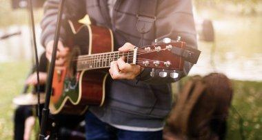 guitarist playing in autumn park, crop
