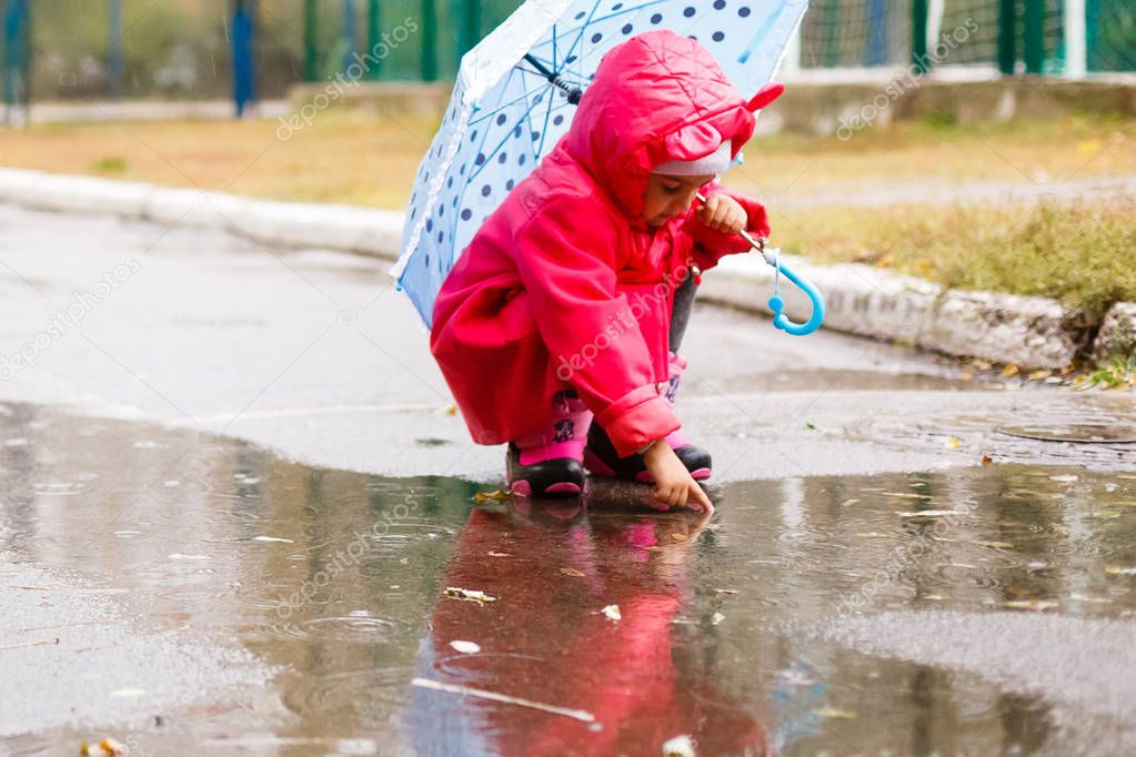 Adorable little girl with colorful umbrella playing in puddle outdoors at autumn rainy day