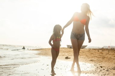 Young mother with daughter having fun and resting on sandy beach