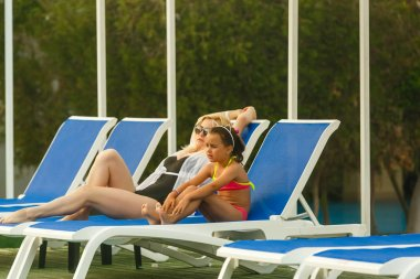Young mother with daughter resting by swimming pool