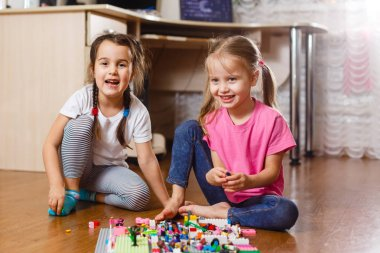 Two little girls playing with erector set at home