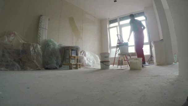 Young man doing repair works in new apartment