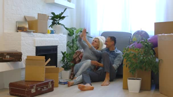 Young couple discussing ideas while sitting on floor near fireplace at home