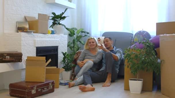 Mladý pár se smíchem a zatímco sedí na podlaze krbu doma při pohledu na fotoaparát