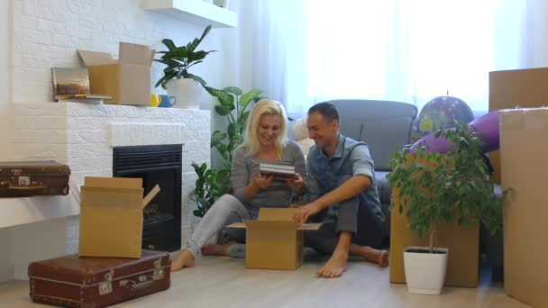 Young couple taking family albums from cardboard box while sitting on floor at home