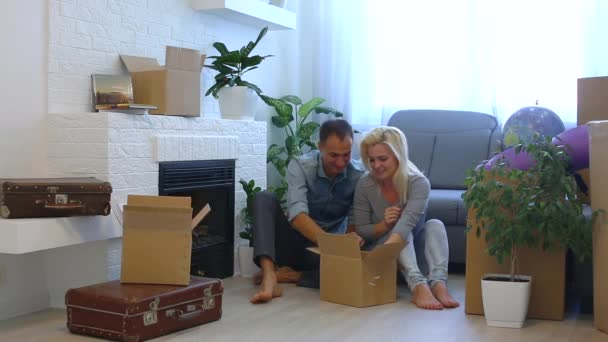 happy young couple taking cups from cardboard box while sitting on floor at home