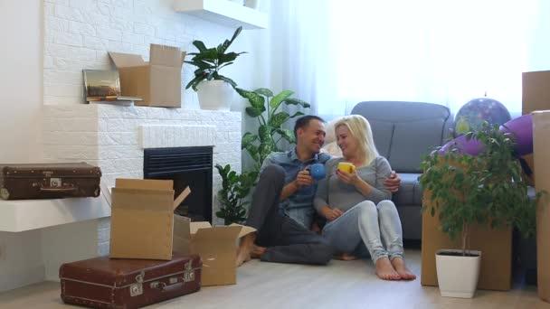junges Paar plaudert und umarmt, während es mit Kaffeetassen am heimischen Kamin auf dem Boden sitzt