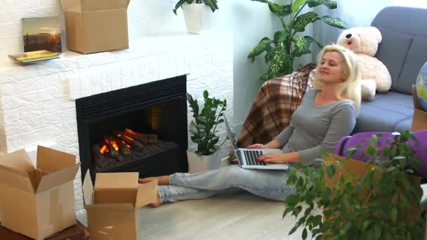 Young woman using laptop and sitting on floor near fireplace at home