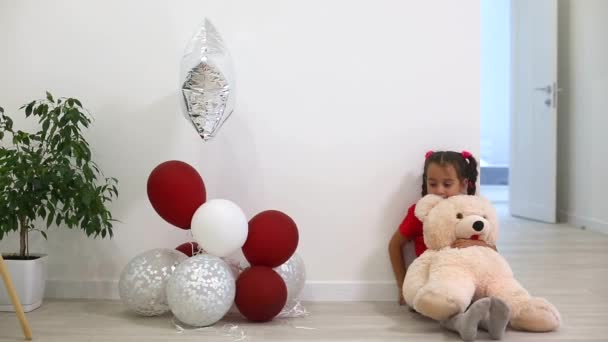 little girl hugging bear toy and having fun with colorful balloons at home