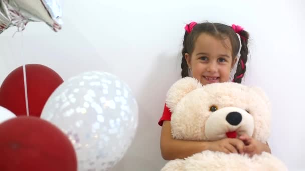 pretty girl holding bear toy and playing with balloons on white wall background