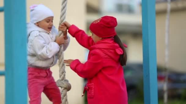 Two preschool girls playing on playground